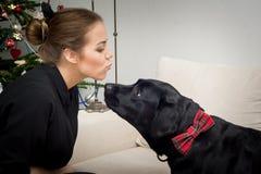 Jeune femme embrassant le chien de Noël Photographie stock libre de droits