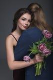 Jeune femme embrassant son ami avec le bouquet des pivoines Images libres de droits