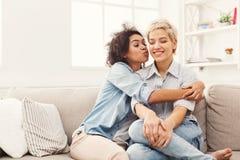 Jeune femme embrassant son ami sur la joue Photographie stock