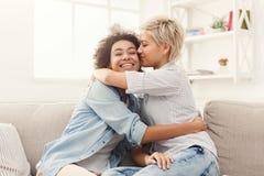 Jeune femme embrassant son ami sur la joue Photo stock