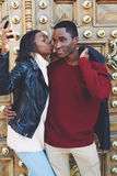 Jeune femme embrassant son ami sur la joue tout en faisant l'autoportrait avec l'appareil photo numérique intelligent de téléphon Images libres de droits