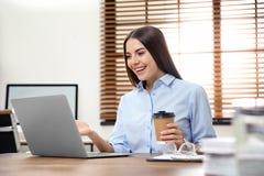 Jeune femme employant la causerie visuelle sur l'ordinateur portable photos stock