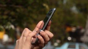 Jeune femme employant Smartphone dans des messages d'OutdoorWriting sur le smartphone banque de vidéos