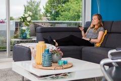 Jeune femme employant un à télécommande sur le divan photo libre de droits