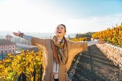 Jeune femme en automne se réjouissant dehors Photos stock
