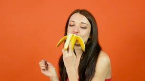 Jeune femme en bonne santé avec la peau parfaite mangeant la banane sur le fond orange lumineux Fruits tropicaux Consommation vég clips vidéos