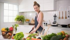 Jeune femme en bonne santé dans des légumes d'une coupe de cuisine image stock