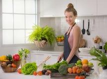 Jeune femme en bonne santé dans des légumes et la préparation d'une coupe de cuisine du repas sain photographie stock