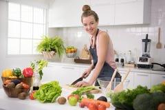 Jeune femme en bonne santé dans des légumes et la préparation d'une coupe de cuisine du repas sain images libres de droits