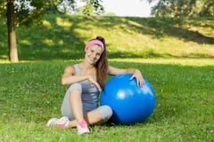 Jeune femme en bonne santé de forme physique avec la boule de Pilates extérieure Photo libre de droits