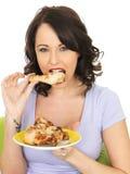 Jeune femme en bonne santé mangeant la jambe de poulet cuite par froid Photos stock