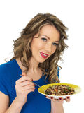 Jeune femme en bonne santé mangeant la zizanie et le Bean Salad mélangé Photographie stock