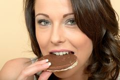 Jeune femme en bonne santé mangeant un gâteau de riz de chocolat Photos libres de droits