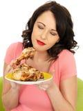 Jeune femme en bonne santé rêveuse tenant le pilon de poulet cuit par froid Image stock