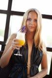 Jeune femme en café avec le cocktail frais Images stock
