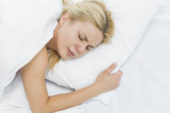 Jeune femme en douleur se trouvant sur le lit Image stock