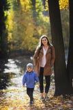 Jeune femme en parc en automne avec un enfant Mère avec le fils images libres de droits