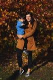 Jeune femme en parc en automne avec un enfant Mère avec le fils photos stock