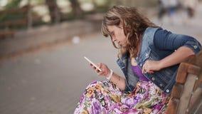 Jeune femme en parc vert d'été avec un smartphone à disposition Dactylographiez les messages et les sourires clips vidéos