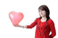 Jeune femme en rouge avec le ballon en forme de coeur Image stock