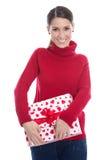 Jeune femme en rouge d'isolement avec un présent pour la valentine ou le chri Photos libres de droits