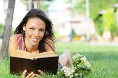 Jeune femme en stationnement, livre et relevé verts image libre de droits