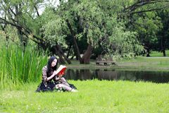 Jeune femme en stationnement, livre et relev? verts Bonheur, beau photos stock