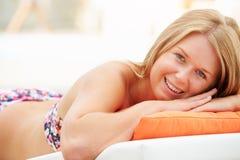 Jeune femme en vacances détendant par la piscine images stock