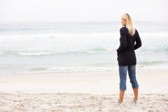 Jeune femme en vacances restant sur la plage de l'hiver Images stock