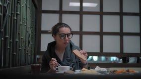 Jeune femme en verres élégants prenant le déjeuner banque de vidéos