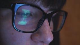 Jeune femme en verres regardant le smartphone et surfant l'Internet L'écran du téléphone est reflété dans banque de vidéos