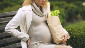 Jeune femme enceinte avec le sac à provisions ayant le repos sur le banc, douleur dans le dos banque de vidéos