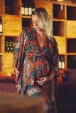 Jeune femme enceinte blonde touchant son ventre et regardant loin images libres de droits