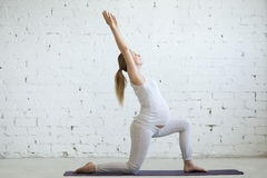 Jeune femme enceinte faisant le yoga Virabhadrasana 1 pose Photographie stock