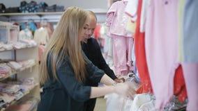 Jeune femme enceinte heureuse choisissant les vêtements nouveau-nés à la vidéo de longueur d'actions de magasin de boutique de bé banque de vidéos
