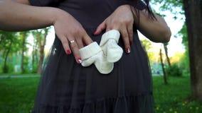 Jeune femme enceinte heureuse jouant avec des butins de bébé sur son ventre enceinte Photographie stock libre de droits