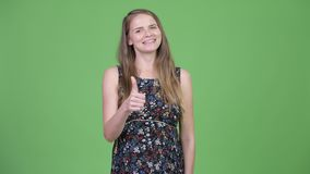 Jeune femme enceinte heureuse renonçant à des pouces banque de vidéos