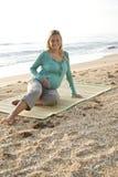 Jeune femme enceinte heureuse s'asseyant sur le couvre-tapis à la plage photographie stock libre de droits