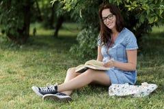 Jeune femme enceinte lisant son livre en parc image stock