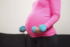 Jeune femme enceinte s'exerçant avec les poids s'exerçants d'intérieur Images libres de droits