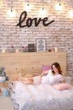 Jeune femme enceinte se trouvant sur le lit dans la robe blanche, amour d'inscription sur le mur de briques Photo stock