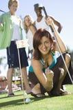 Jeune femme encourageant tout en jouant le golf Photos libres de droits