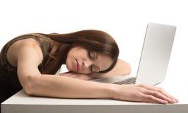 Jeune femme endormie à l'ordinateur portable photographie stock libre de droits