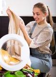 Jeune femme enlevant la machine à laver de vêtements photographie stock libre de droits