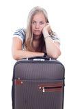 Jeune femme ennuyée se déplaçant avec le bagage Photo stock