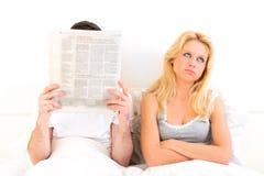 Jeune femme ennuyée tandis que ses actualités de lecture de garçon Image stock