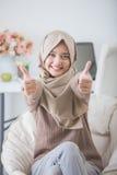 Jeune femme enthousiaste avec le hijab souriant à l'appareil-photo et montrant thu images libres de droits
