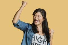 Jeune femme enthousiaste avec le poing augmenté tout en regardant loin au-dessus du fond coloré Photo stock