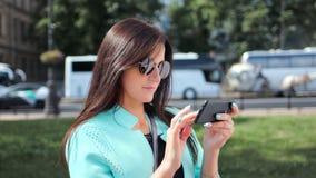 Jeune femme enthousiaste de voyage dans des lunettes de soleil utilisant le smartphone au fond ensoleillé de paysage urbain clips vidéos