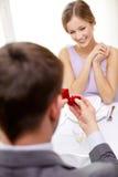 Jeune femme enthousiaste et ami donnant son anneau Photographie stock